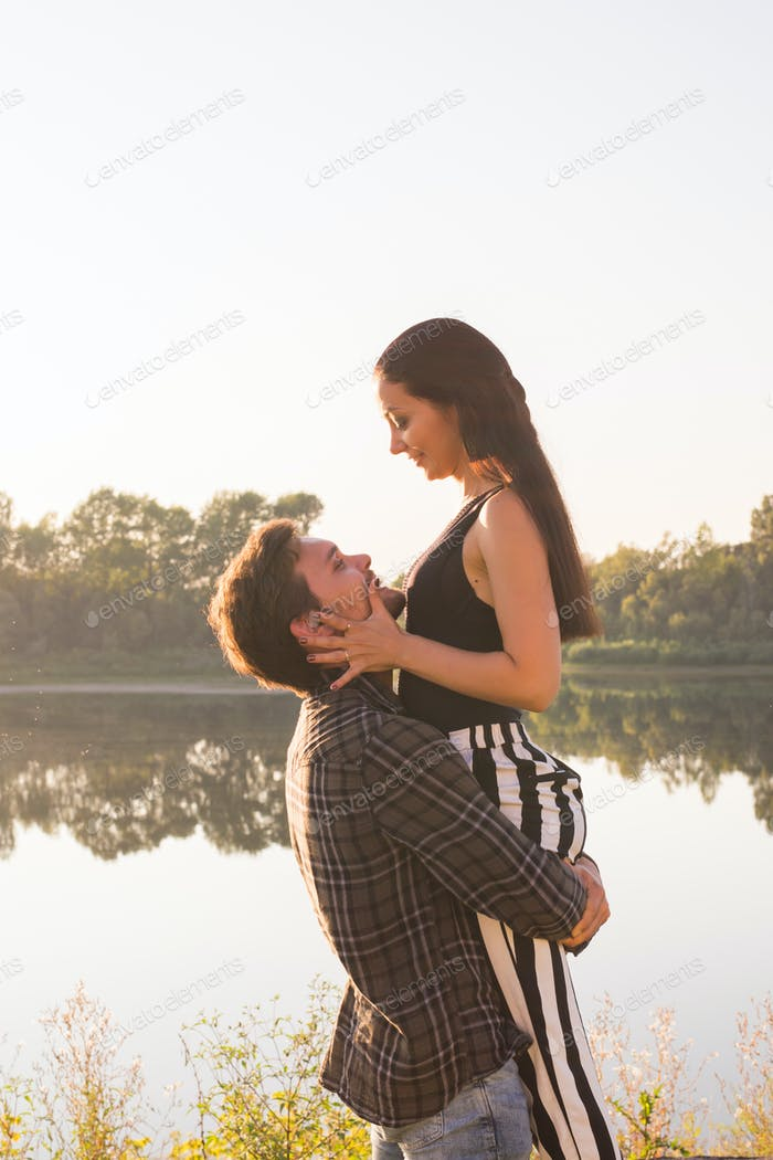 People, love and nature concept - Man holding woman in his arms over nature background
