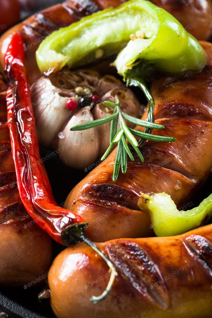 Fried bbq sausages with  vegetables in iron pan.