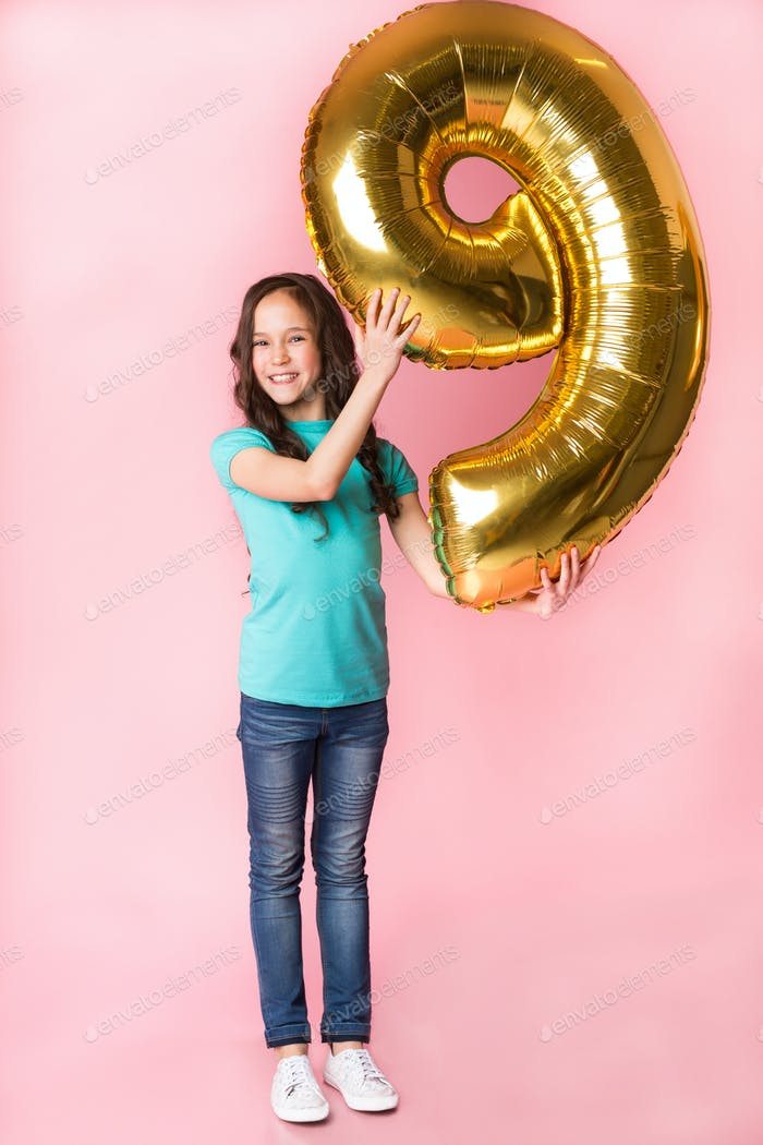 Excited girl with number 9 balloon at studio background