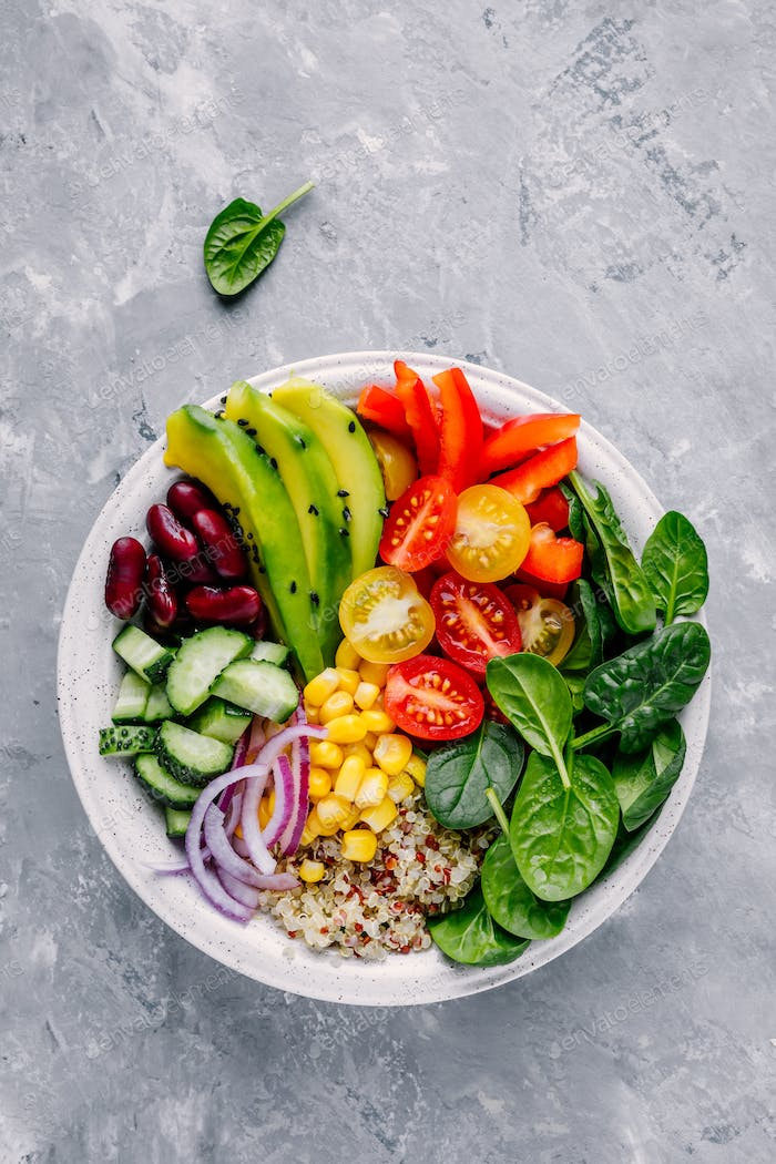 Buddha bowl. Avocado, quinoa, tomato, cucumber, red beans, spinach, red onion and red paprika