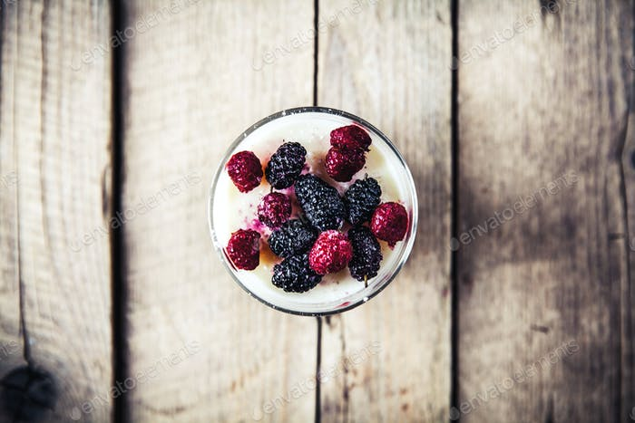Healthy breakfast - Dairy yogurt with raspberry, mulberry on wooden background