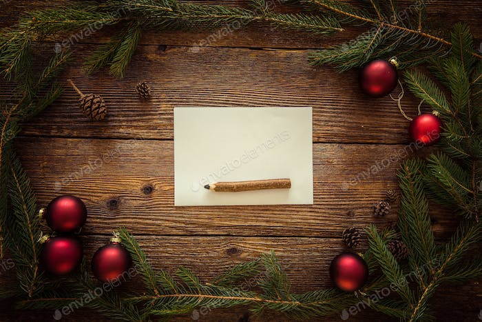 Fir Tree Branch, Red Balls and Paper on Wooden Table. Letter to Santa. Space for Text