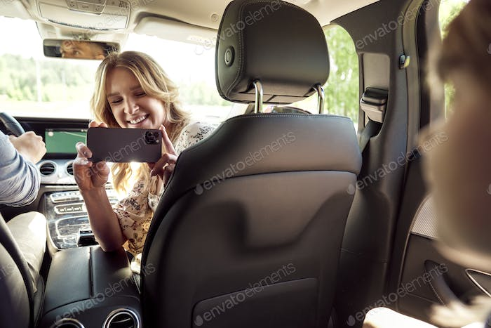 Mother taking pictures of her child in the car