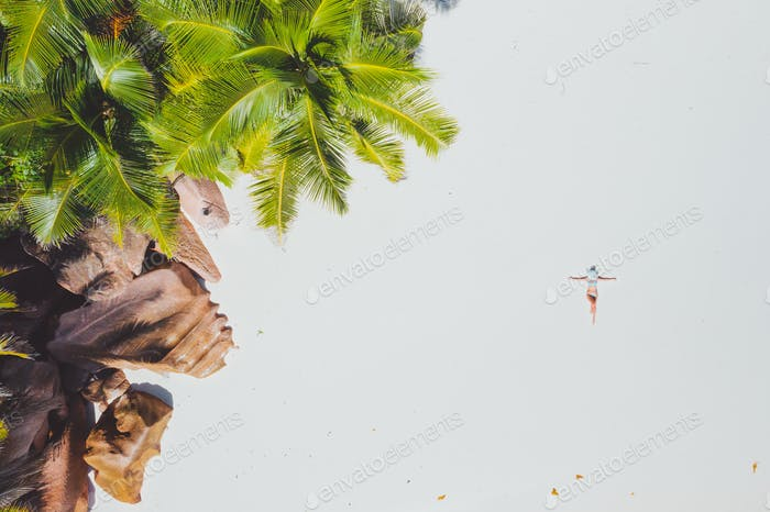 Aerial photo of young woman laying on exotic tropical beach with white sand. Girl sunbathing and