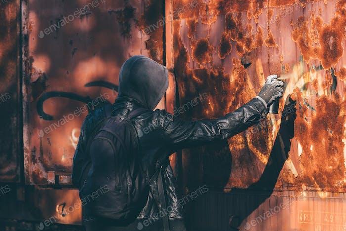 Hombre sin hogar pintura aerosol viejo vagón tren con lata de aerosol