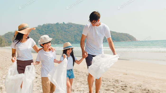 Asian young happy family activists collecting plastic waste and walking on beach.