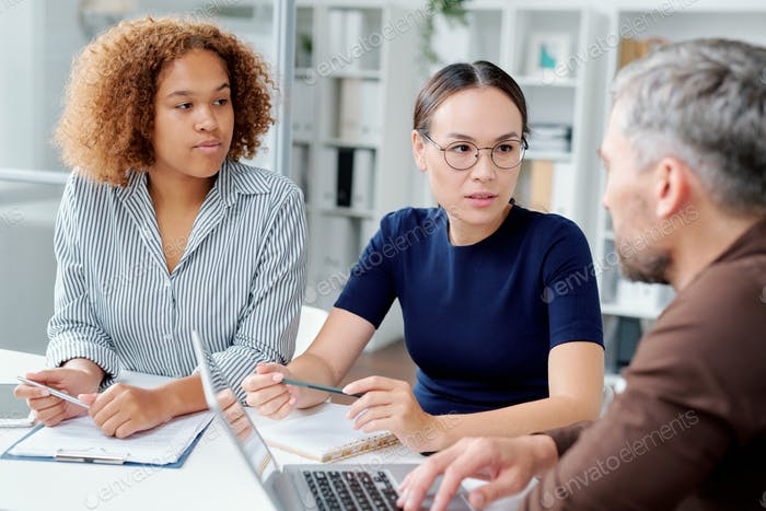 Two young intercultural female subordinates consulting with their boss