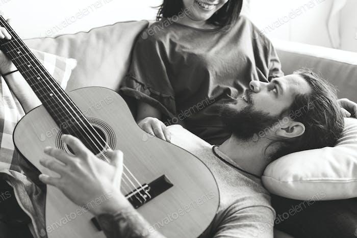 Niedlich paar auf einer Couch Freund spielen eine Gitarre Musik und Liebe Konzept