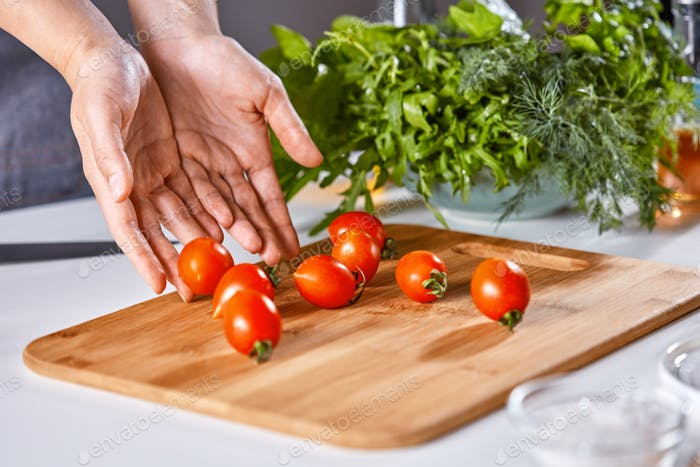 Woman's hands are putting ripe cherry tomatoes on a wooden board on the kitchen table with