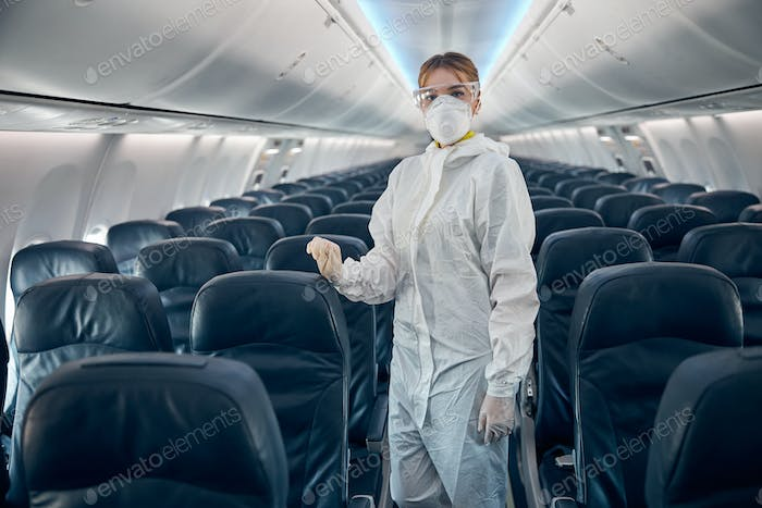 Female flight attendant standing on the salon of civil airplane in protective glasses