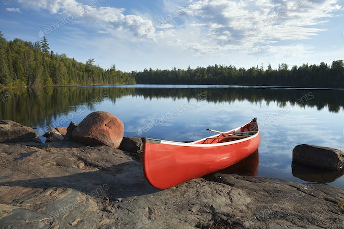 Red canoe on rocky shore of Boundary Waters lake in northern Minnesota