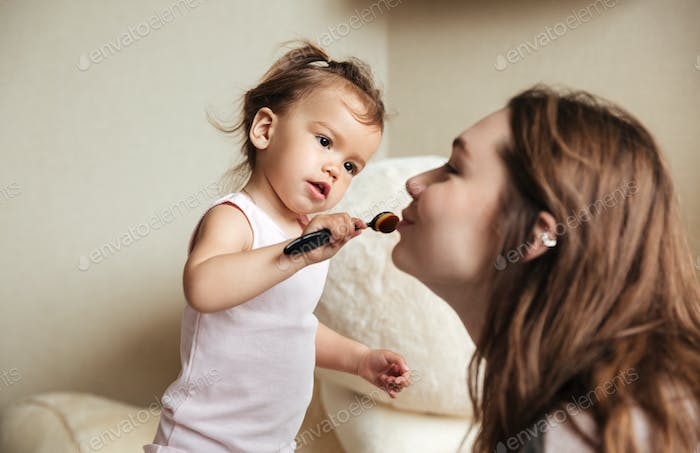 Little cute girl does a makeup for her happy mother