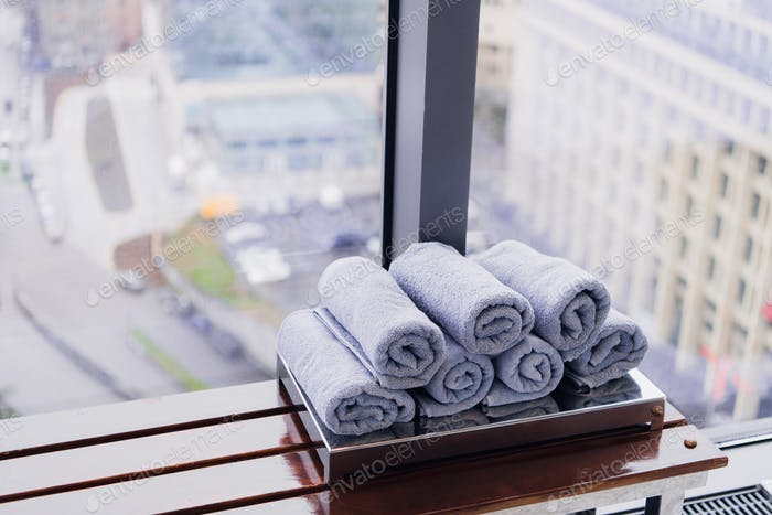 Stack of rolled towels in hotel at gym with city view