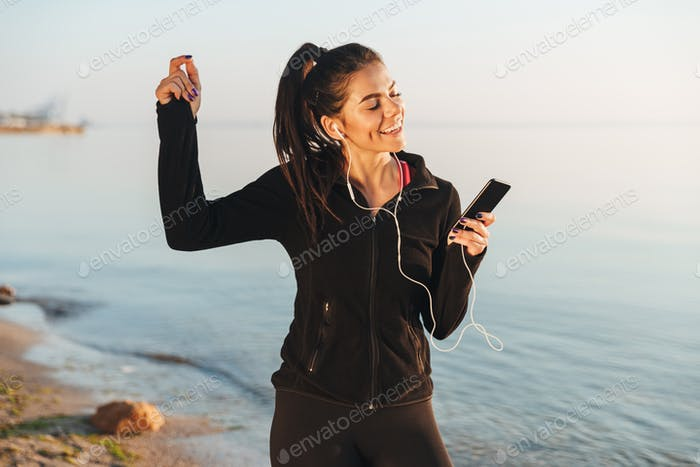 Delighted young sportswoman listening to music