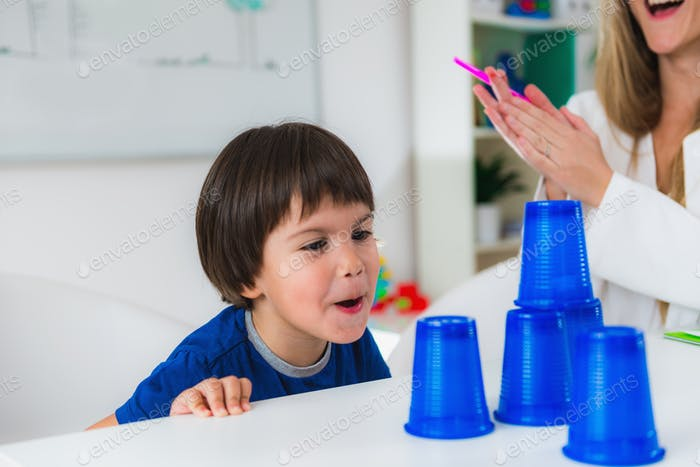 Child psychology, toddler doing tests with plastic cups