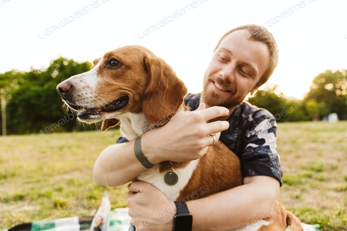 Image of young man smiling and sitting with his beagle dog in park