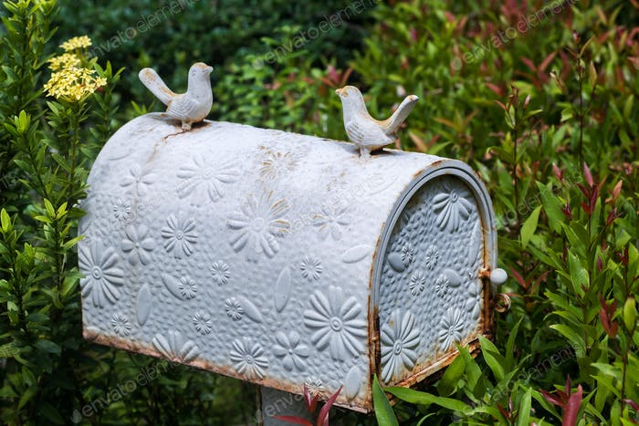Old vintage white postbox with flowers pattern