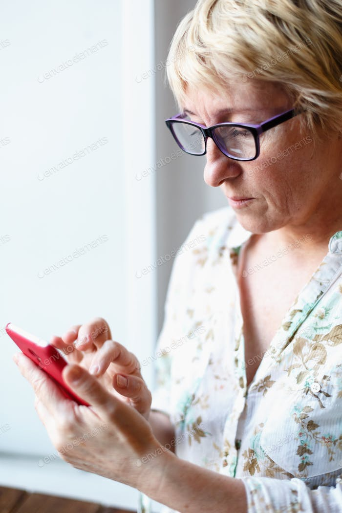 Mature female in glasses using smartphone