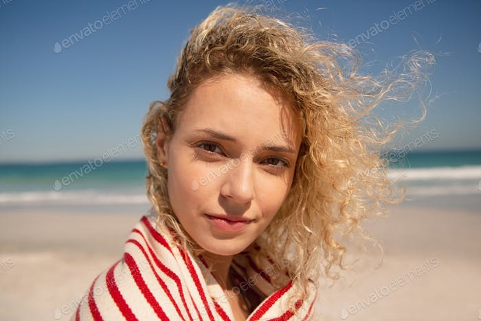 Portrait of Caucasian beautiful woman wrapped in towel standing on the beach