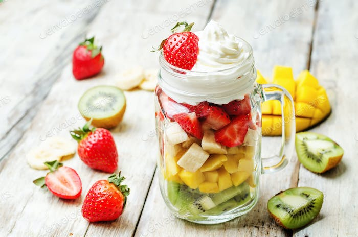 Kiwi strawberry banana mango salad with whipped cream