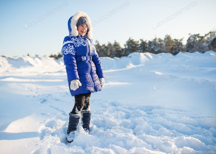 Positive laughing girl in a blue winter coat