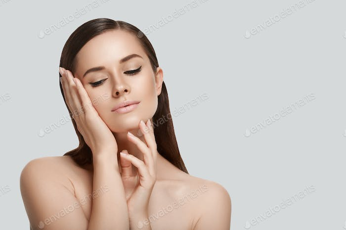 Beautiful woman face close up hand touching face gray background