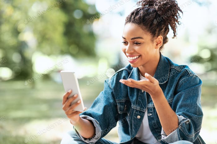 Cheerful Black Lady With Phone Making Video Call Sitting Outdoors