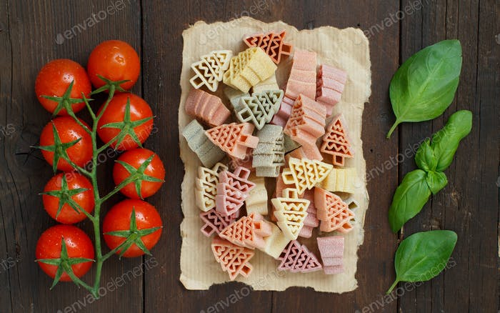 Tricolor fir tree shaped pasta, tomatoes and basil on wood