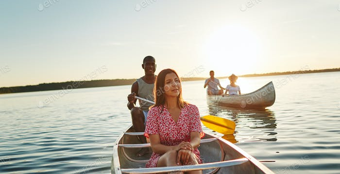 Young friends enjoying the day canoeing together on a lake
