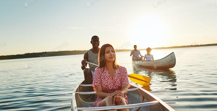Junge Freunde genießen den Tag mit dem Kanufahren auf einem See