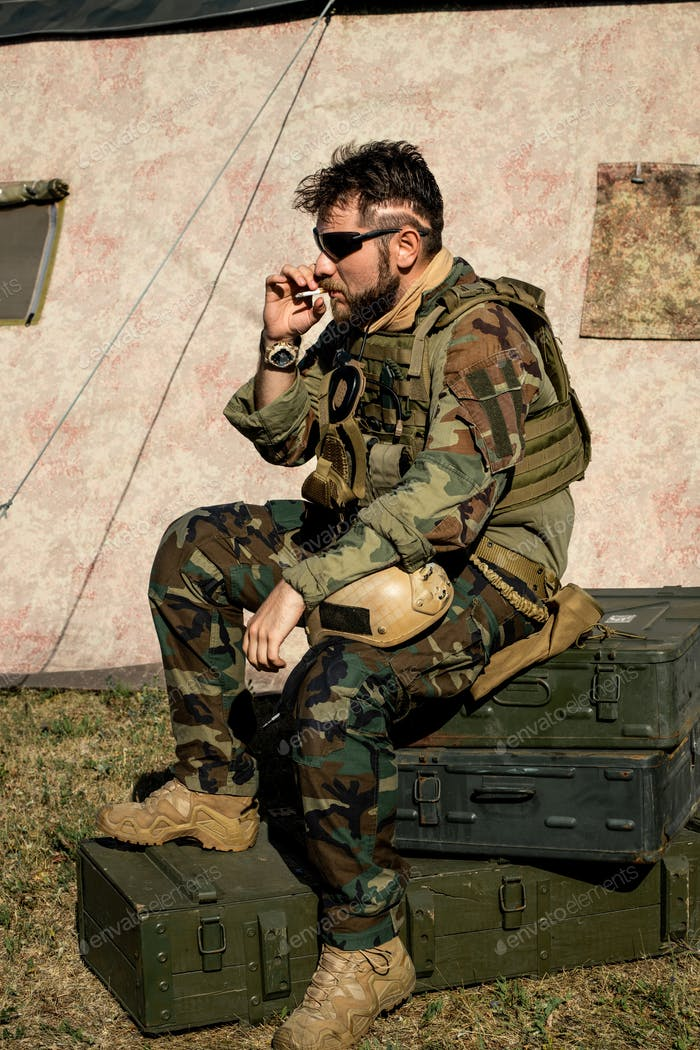 Smoking man in camouflage outfit