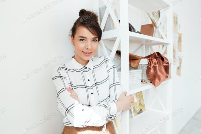 Young smiling woman fashion designer standing at her studio