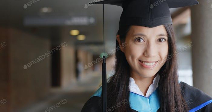 Frau mit Abschlusskleid im Universitätskleid