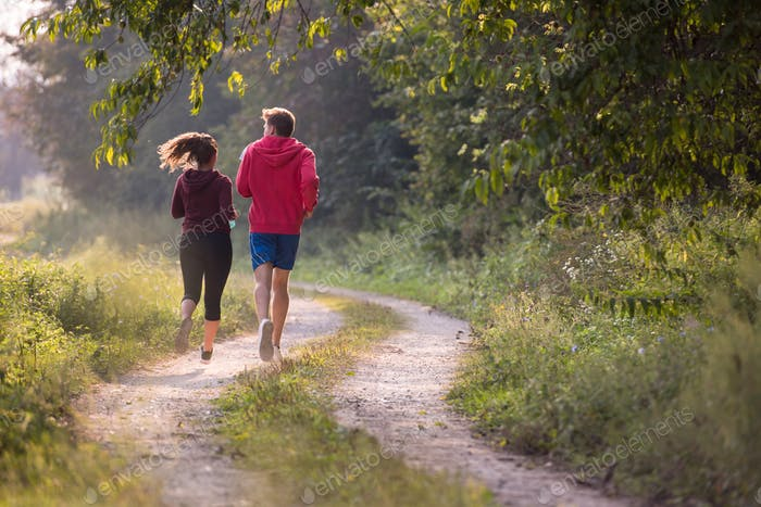 young couple jogging along a country road
