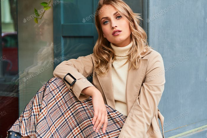 Beautiful casual blond girl in stylish trench coat and skirt confidently looking in camera outdoor