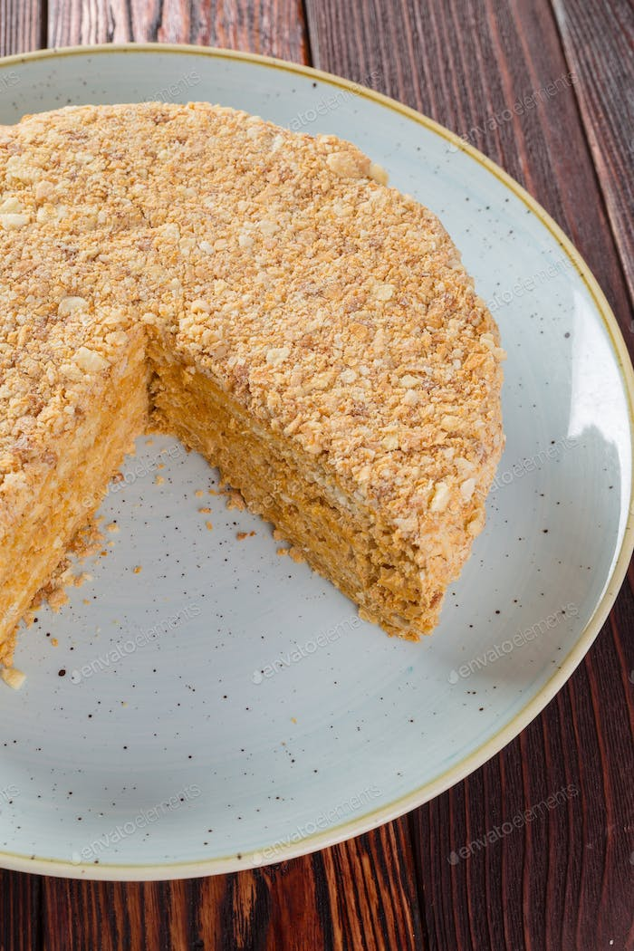Cut caramel cake on plate on wooden table