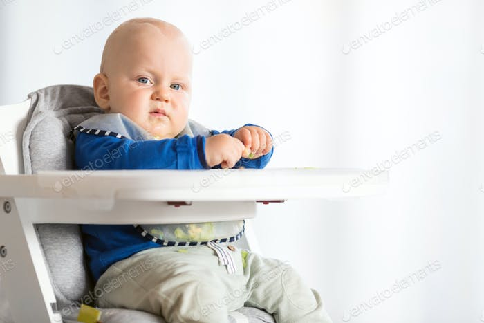 Baby boy eating with BLW method, baby led weaning
