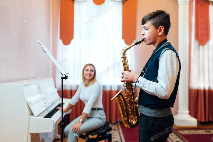A student boy in a saxophone lesson learns to play accompaniment of a cheerful teacher on the piano