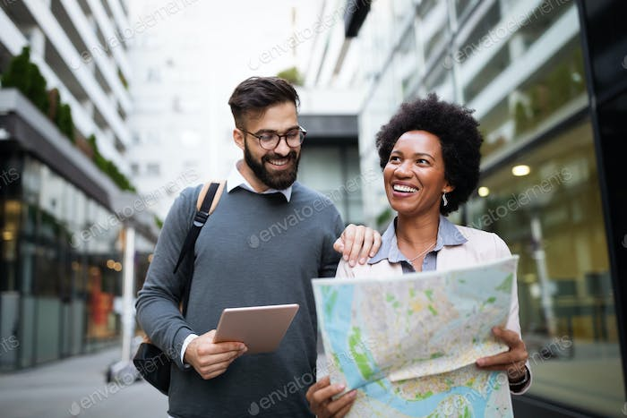 Happy tourists sightseeing city with map. Travel, people, fun concept