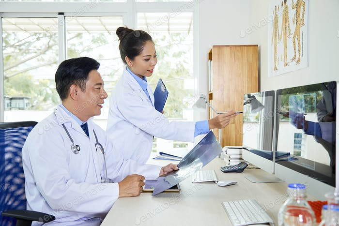 Doctor Helping Colleague With Diagnostication