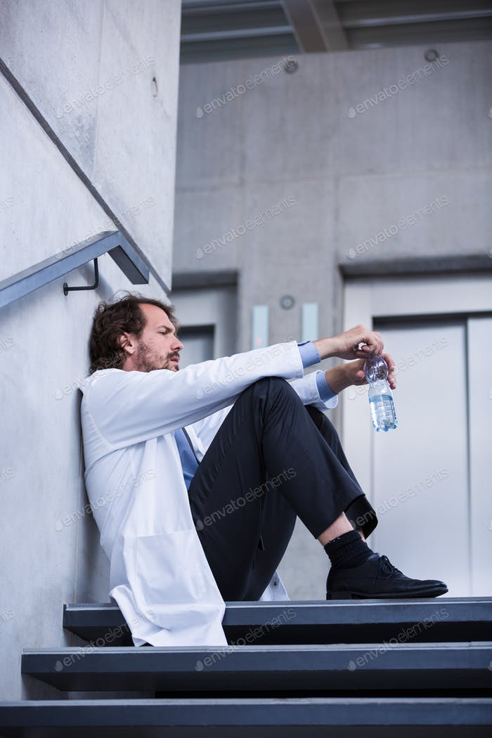 Worried doctor sitting on stairs
