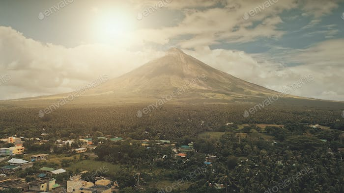 Aerial volcano erupt at sunlight closeup. Sun cityscape of rural town at green volcano valley