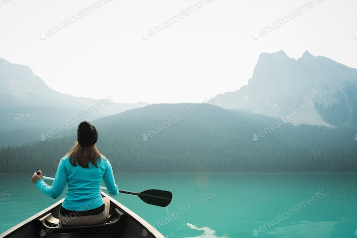 Rear view of young Caucasian woman kayaking in lake with mountains in the background