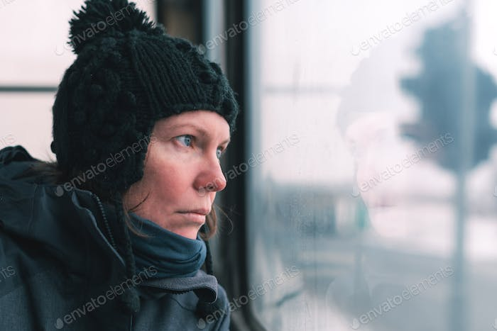 Sad woman on the bus looking through window