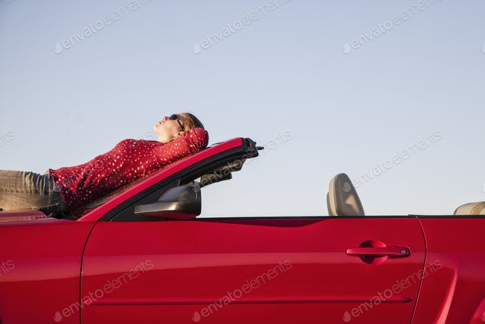 A Caucasian woman  resting on the hood of her convertible sports car at a rest stop.