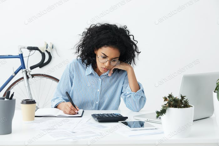 Candid shot of confident hardworking young businesswoman with curly hair sitting at her desk in whit