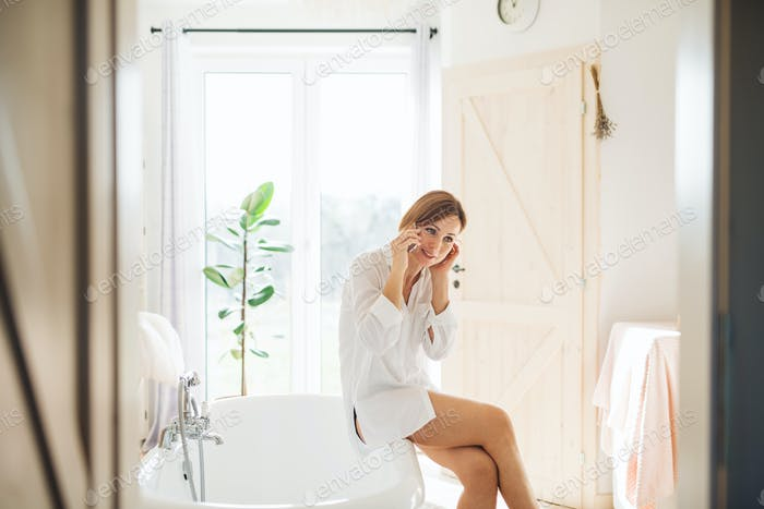 A young woman with smartphone in the morning in a bathroom, making a phone call.