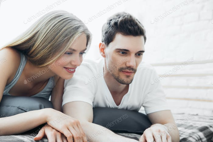 Cheerful young loving couple sitting sofa home and looking at laptop and mobile phone