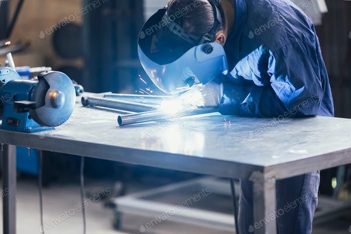 Man in mask welding iron bars