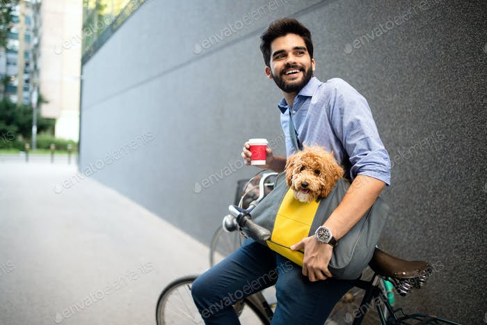 Handsome young man sitting on bike and holding coffee cup on street
